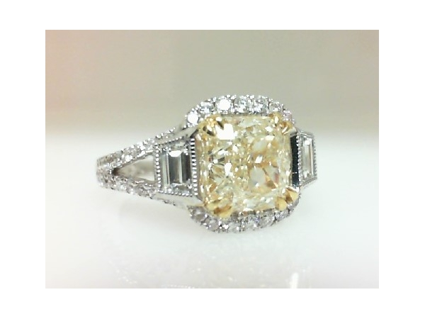 Diamond Fashion Ring - Ladies 18 karat white and yellow gold fancy yellow diamond ring. This ring features one prong set cushion cut yellow diamond totaling 2.22 cts.  The diamond is VS1 clarity. Flanking the center diamond are two bezel set trapezoid diamonds totaling 0.37 ct. Accenting the ring are 54 prong set round brilliant cut diamonds totaling 0.49 ct. These diamonds are G color, VS1 clarity. The ring is a size 6.50 and weighs 5.70 grams.  EGL Report # EGLUS912367201D