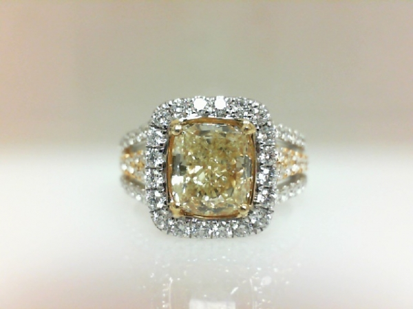 Diamond Fashion Ring - Ladies 18 karat white and yellow gold fancy yellow diamond ring. This ring features one prong set cushion cut yellow diamond totaling 2.02 cts. The diamond is VS2 clarity. Accenting the ring are 78 prong set round brilliant cut diamonds totaling 0.98 ct. These diamonds are G color, VS1 clarity. The ring is a size 6.50 and weighs 7.20 grams.