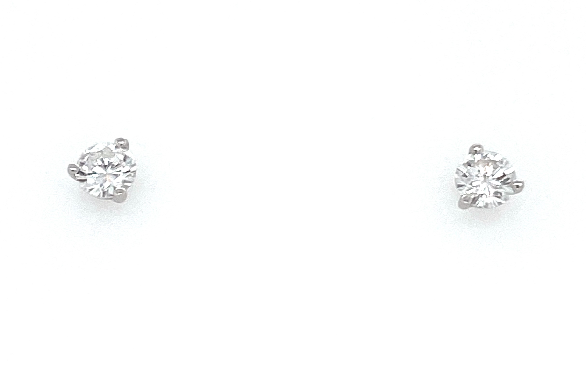 Diamond Stud Earrings - Ladies 14 karat white gold high polished diamond april birthstone stud earrings.  These earrings feature two 3-prong set round brilliant cut diamonds.  The diamonds are G-H color,  I1 clarity and weigh 0.50 ct.  The earrings have friction posts and backs and weigh 0.60 grams.