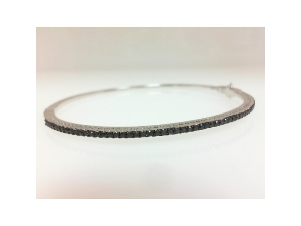 Diamond Bracelet - Ladies 18 karat white gold black diamond bangle bracelet. This high polished bangle features 57 prong set round brilliant cut black diamonds totaling 0.53 ct. The bangle measures 7.00 inches in length with a hidden clasp and safety and weighs 8.10 grams.