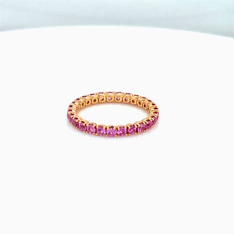 Colored Stone Ring - Ladies 18 karat rose gold high polished sapphire eternity ring.  This ring features 27 prong set round pink sapphires totaling 1.30 cts.  This ring weighs 1.70 grams and is size 6.00.