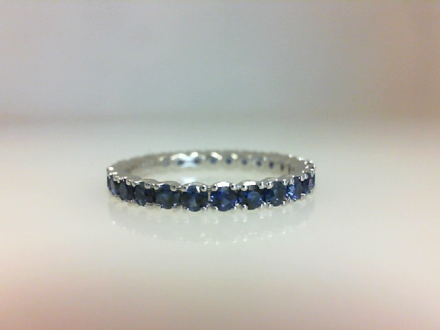Colored Stone Ring - Ladies 18 karat white gold high polished sapphire eternity band.  This band features 27 prong set round blue sapphires totaling 1.30 cts.  This ring weighs 1.80 grams and is size 6.00.