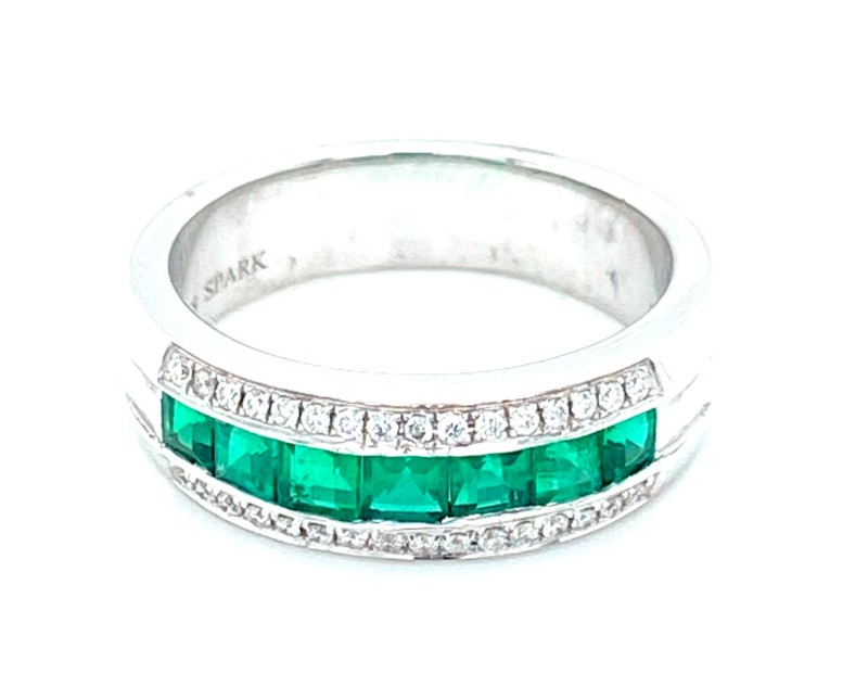 Colored Stone Ring - Ladies 18 karat white gold high polished emerald and diamond ring.  This ring features seven channel set square emeralds totaling 0.77 ct.  Bordering the emeralds are 32 prong set round diamonds totaling 0.16 ct.  This ring weighs 7.40 grams and is size 6.50.
