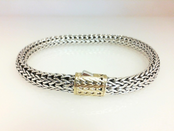 Fashion Bracelet - Ladies sterling silver and 18 karat yellow gold Classic Chain Collection bracelet designed by John Hardy. This 7.00 mm wide high polished and detailed bracelet measures 7.50 inches in length with a decorative clasp and weighs 27.10 grams.