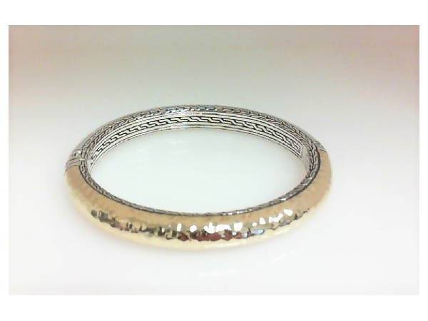 Fashion Bracelet - Ladies sterling silver and 18 karat yellow gold Classic Chain Collection bangle designed by John Hardy. This high polished and hammered 8.50 mm oval hinged bracelet measures 7.50 inches in length and weighs 37.60 grams.