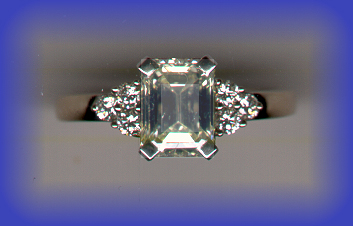 Engagement Ring - 18K/Platinum Engagement ring: GIA Certified Center 2.12 Ct Emerald cut SI1/N, very good finish, and 6-side full cut diamonds; Grand Total 2.40 carats.